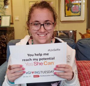 Isabelle holding a Giving Tuesday UnSelfie sign