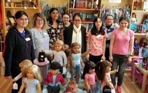 trainees standing with American Girl dolls